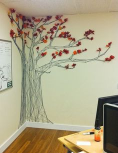 A tree mural, made of black yard, push pins and paper leaves.