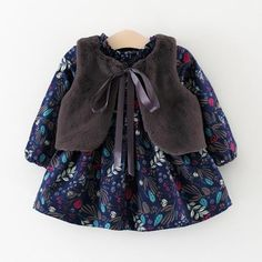 * Floral print<br /> * Back zipper<br /> * Warm and comfy<br /> * Material: 67.9% Polyester, 32.1% Cotton<br /> * Machine wash, tumble dry<br /> * Include: 1vest, 1 dress<br /> * Imported<br /> <br /> Pretty floral pattern and soft fleece vest make this 2-piece set one of the loveliest clothes in your girl's wardrobe.