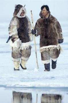 Inuit men in traditional dress on the ice in Nunavut Territory, Canada.