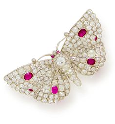 A diamond and ruby butterfly brooch, French  set throughout with old mine, European, rose and single-cut diamonds, highlighted with collet-set oval and marquise-cut rubies; with French assay marks; estimated total diamond weight: 16.50 carats; mounted in platinum and white gold; length: 3in.