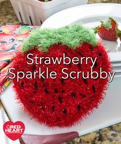 Strawberry Sparkle Scrubby Free Crochet Pattern in Red Heart Scrubby Sparkle Yarn - Since this scrubby is a double thickness, it's a nice sturdy scrubber for any cleaning task (and you can embroider the seeds while hiding the thread between the layers). Crochet it to help you in the kitchen, then throw it in the washer and air dry.