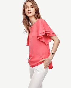 "Flutter sleeves add breezy femininity to this double-layered crepe top, finished with a pretty back peplum detail. Jewel neck. Flutter sleeves. Back keyhole with button closure. Back peplum. 25"" long."