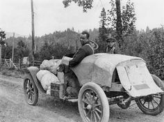 Man, boy and dog head up the McKenzie River for camping trip in what appears to be a homemade motor vehicle comprised of sheets of metal fastened to chassis. Camping gear is strapped to running board where dog rides. Fence borders dirt road; forested ridge in background. c.1918