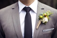 grey suit, navy tie, buttonhole wrapped in twine