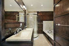 Compact bathroom decked out in dark hardwood all around, featuring marble sinks, bath and glass-enclosed shower.