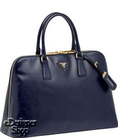 679.00 *Color: Royal Blue *Patent saffiano leather with goldtone hardware *Triangle with metal lettering logo *Double handles with removable ID tag *Two way zip closure *Four metal feet at base *Logo jacquar...