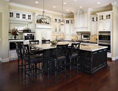 Cosa Belle Interiors: transitional kitchen Featuring, white raised cabinets with true divided lite glass with in cabinet lighting, black Quartz countertops, island with black raised cabinets with granite countertops, dark wood floors and built in bar height island extension.