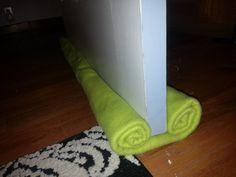 DIY Door Draft Stopper: simply roll fabric or blanket and safety pin.