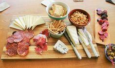 Mooie binnenkomer! Hartige plank als binnenkomst op een Tapasfeestje. Kaas worst toast en olijven met ansjovis plank
