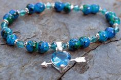What you see is what you get - this is the only one of this bracelet I will make! Get it before its gone! - 6mm imitation chrysocolla acrylic beads. - Blue faceted crystal charm in stamped .925 silver. - Swarovski-inspired crystal bicone beads. - Silver tone spacer beads. - 6 Inches un-stretched (approximately). This bracelet best fits people with a small frame. - Ships from Canada.  Chrysocolla is the stone of love, so what better charm to put on this delicate bracelet than a blue heart…