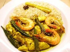 Yellow fish curry with skin-on, Cornish hake fillets, black tiger prawns & chipirones with okra in aThai, yellow, curry sauce served with Thai fragrant rice.