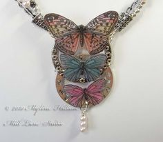 Mixed Media Butterfly Necklace featuring butterflies cut out from scrapbook paper which were then coated with resin. Includes a tutorial on how to create your own epoxy resin stickers by Myléne Hillam of Mill Lane Studio.