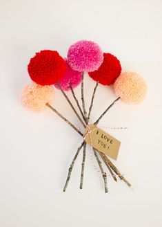pom pom flowers--possibly use a few for table center piece.....different colors, with brown twine looking stem....in a cute glass vase?