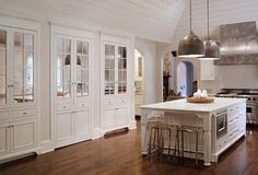 This kitchen has so much charm... Built-ins, panelling, and oversized brushed metal pendent lights!