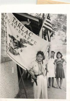 1945- 22-year-old Philippine girl who fought guerrilla forces in the Tarlac area of Luzon, poses with her gun, her cartridge belt and the Tarlac flag.