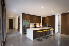 Simple modern kitchen with a white countertop and brown cabinets. Nice accent yellow barstool seats!
