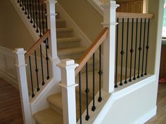Nice staircase with light wood-and-white railing and wrought-iron balusters. …