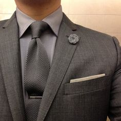 monochromatic look in shades of grey, tie clip & lapel flower
