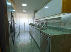 Cozinha pensada para durar. No piso  e bancadas quartzito verde. Para a área de serviço foi instalada porta de correr em vidro piso/teto  no acabamento jateado.