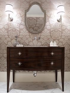 "retrofitted the bureau into a one-of-a-kind sink vanity and custom-designed the polished-nickel starburst drawer-pulls.  Other touches include Carrera marble floor tiles; modern, wall-mounted tap fixtures; elegant, Barbara Barry-designed torch sconces; and bold-patterned damask wallpaper.  ""If you use a large repeat-patterned paper in a small space, it makes the room feel large and continuous,"""