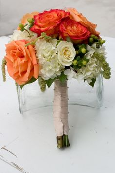 Two tones of orange roses, white hydrangea and hanging amaranths.
