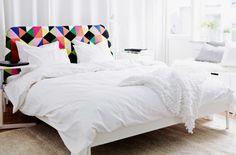 Spálňa s posteľou, stolíkom na laptop, stojacou lampou, kobercom a lavicami s úložným priestorom IKEA.