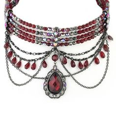 Inspired by old Hollywood glamour, this costume choker necklace has four wire strands of red and gray metallic beads that glimmer in every direction. Sparkling red aurora borealis crystals are encased inside three linear metallic connectors, used to drape the center with delicate hematite chains. With a Moulin Rouge-esque vibe, the necklace is topped off by a ruby red jewel pendant that is outlined in a dainty filigree pattern.