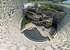 Shanghai Natural History Museum. Perkins + Will designed the structure, which expresses architectural themes found in nature. A green roof rises from the site plan, spiraling logarithmically like the shell of a nautilus.