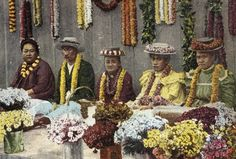 Photo of c.1900 Lei makers sitting in a row surrounded with fresh flowers, close-up, postcard (HAWAII)