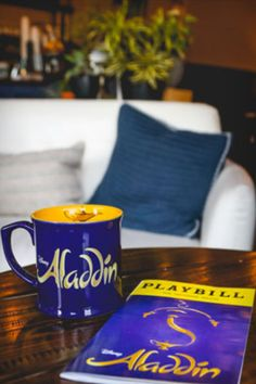 Inspired by the Genie's lamp, this whimsical coffee mug features the show's logo on the outside, and the Genie art on the inside. Purple/yellow, dishwasher and microwave safe. Make your wish and we deliver. Broadway Plays, Broadway Theatre, Musical Theatre, Genie Lamp, Purple Yellow, Aladdin, Hamilton, Microwave, Theater