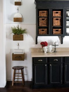 Wicker baskets and plants bring life to this kitchen designed by Layla Palmer. A beadboard backsplash evokes a casual look to the space, and vintage hanging planters represent the weathered look often associated with coastal design.