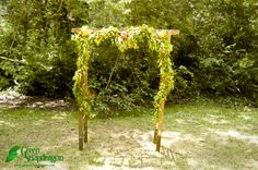 Ceremonial arch made of wooden ladders with garland of bay laurel, seeded eucalyptus, wax flower, myrtle, football mums, and peony. At Stern Grove, San Francisco.
