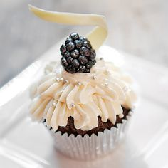 blackberry wedding cupcakes: A cupcake embellished with silver sugar beads is topped with a fresh, juicy blackberry.