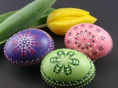 This is a set of three real chicken eggs painted in purple, green and pink and decorated with colored wax. To create the eggs, I use the pinhead method