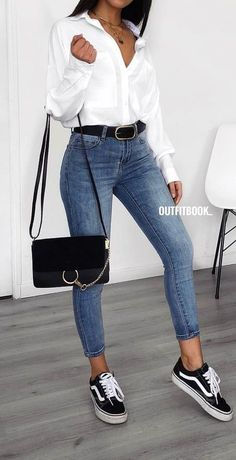 #spring #outfits woman in white button-up long-sleeved shirt, blue denim jeans, and black leather crossbody bag standing near white wall. Pic by @outfitbook_