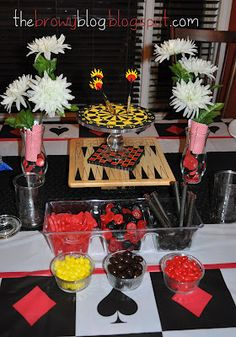 Game boards and dart board as centrepiece. Red, Black and Yellow Candy.