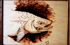 Trout is a bust of a speckled trout watching out for the fly. Burned onto birch plywood this 5x7 picture was framed to sit on an end table or shelf.