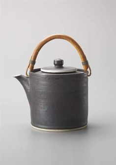 Lucie Rie: Teapot, Stoneware, manganese and white glazes, bamboo and brass handle. 18 cm. (7 in.) high, c.1955