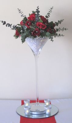 Martini Vase with red silk roses and eucalyptus, acrylic stones and lights in the base of the vase, a circular mirrored base, 4 diamante candle holders with LED tea light candles and a red silk table runner. Martini Glass Centerpiece, Glass Centerpieces, Wedding Centerpieces, Wedding Table, Wedding Decorations, Decor Wedding, Diy Wedding, Silk Roses, Silk Flowers