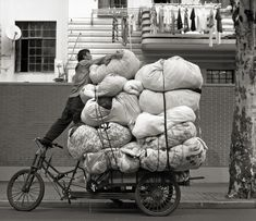 Pile high in a delicate balance. People in Shanghai (and perhaps all over China) go to extraordinary length, regardless of personal safety, in order to make a living. This laundry collection serviceman piled bags of laundry, from this rich neighborhood on ChangLe Lu onto his modified bike retrofitted with a diesel motor. - Charles Yang -