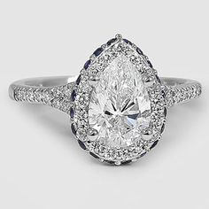 A halo setting is made even more glamorous by vibrant sapphires pavé set around the exterior edge of the halo.