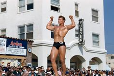 """Photographed by Bob Mizer at Santa Monica's """"Muscle Beach"""" (ca. 1951). Bodybuilding culture and Mizer's photography had a substantial gay following in that earlier era. The Purser Apartments building, visible in the background, still stands at 1659 Ocean Front Walk."""