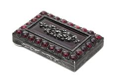 A Diamond, Garnet and Glass-Mounted Silver Snuff Box Late 19th Century the sides and base of the rectangular body engraved with scrolling foliage, the hinged cover bordered with twenty-six cabochon garnets and centered by a garnet-colored glass panel mounted with silver foliage set with diamonds apparently unmarked