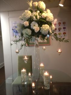 All white tall centerpiece with hanging and floating candles Tall Centerpiece, Centerpieces, Table Decorations, Wedding Bells, Wedding Flowers, Floating Candles, All White, Glass Vase, Furniture