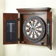 Sierra Dart Board | A deep-toned cabinet conceals this classic dart board set. Includes a professional bristle board , six steel-tipped darts, and a chalkboard on each door for convenient scoring.