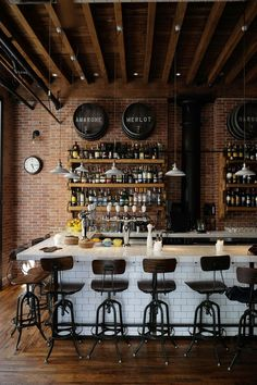 What a stunning bar! The subway tiles mimicking the brick, the pendant lights, wood floors, exposed rafters, the low height and unobtrusive beer taps, and the bar stools with back rest and foot rests: It all says warmth and cozy. C.C. Sic Viresco 3hreebees