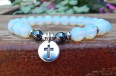 This gorgeous gemstone spiritual bracelet is made with 8mm Opalite and a TierraCast Cross Charm complimented by 6mm Hematite. Simply a beautiful and meaningful bracelet. Opalite Properties: Is called