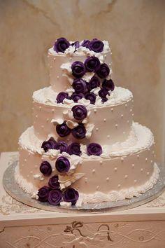 Swiss dot wedding cake with cascading purple flowers