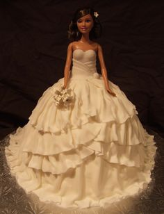 """I baked the Wilton """"wonder pan"""" as well as a 12"""" round (2"""" high) ***Barbie is too tall for just the wonder mold pan! The cake was iced with butter cream icing and then I made THIN fondant ruffles. Each section was done in smaller strips of fondant ruffles so that I could easily form the dress."""