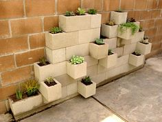 a planter made of cinderblocks stacked against the wall in a very unique way.